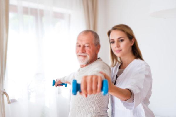 Physio and senior exercising at home