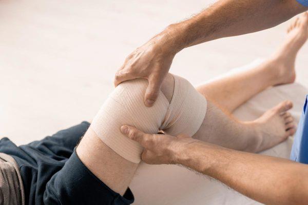 Physio examining knee