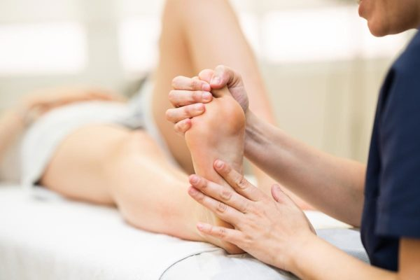 Physio massages a patient's foot